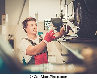 Serviceman checking wheel alignment  in a car workshop