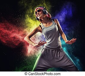 Stylish teenage girl with headphones dancing against...