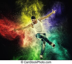 Man dancer showing break-dancing moves against colourful...