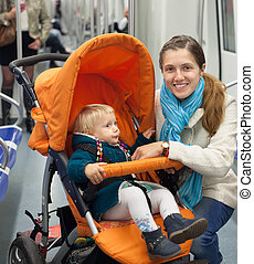 woman with child in stroller at metro