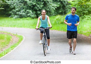 Young sportive couple jogging at the park - View of a Young...