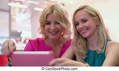 Shopping Online - Two charming ladies sitting in the cafe...