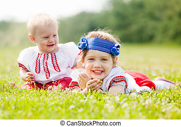 Smiling children in ukrainian folk clothes on grass meadow