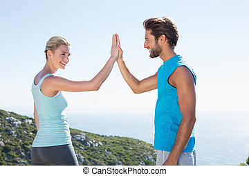 Fit couple standing high fiving on a sunny day