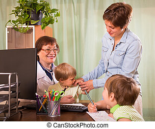 Doctor examining children - Old female pediatrician doctor...