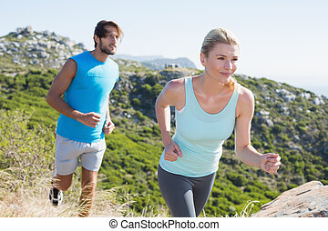 Fit couple jogging through countryside on a sunny day