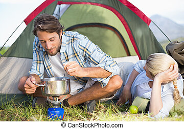 Attractive happy couple cooking on camping stove on a sunny...