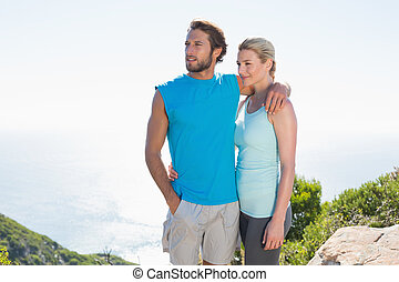 Fit couple standing at summit on a sunny day