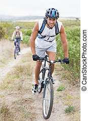 Fit attractive couple cycling on mountain trail on a sunny...