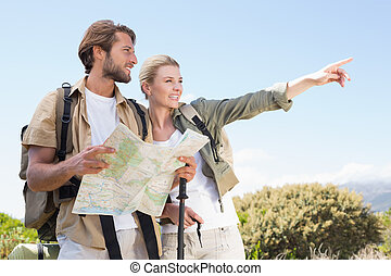 Attractive hiking couple reading the map on mountain trail...