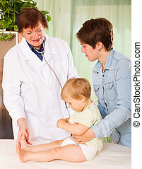 pediatrician doctor examing baby at clinic - Mature...
