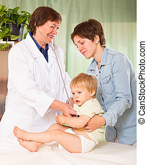 pediatrician doctor examining baby girl with stethoscope at...