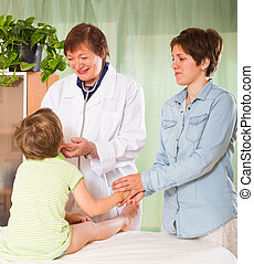 Doctor examining child - Smiling old female pediatrician...