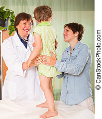 Doctor examining child - Friendly aged female pediatrician...
