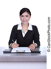 business woman sitting on her desk holding a pen working...