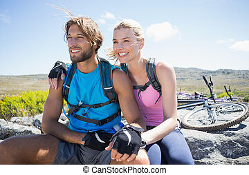 Fit cyclist couple taking a break on rocky peak on a sunny...
