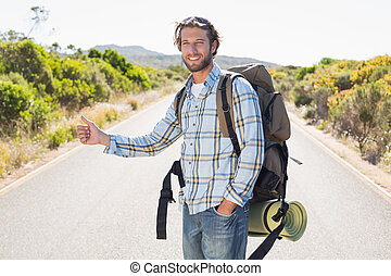 Attractive man hitch hiking on rural road on a sunny day