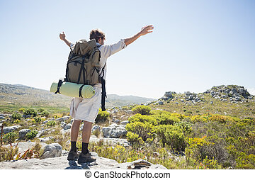 Hiker standing at the summit with arms outstretched on a...