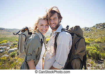 Hiking couple standing on mountain terrain smiling at camera...