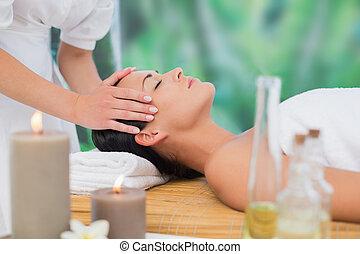 Beautiful brunette enjoying a head massage at a luxury spa