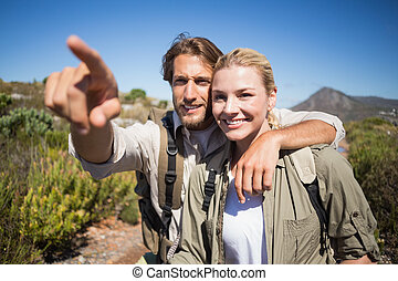 Happy hiking couple walking on mountain terrain on a sunny...
