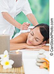 Beautiful brunette enjoying a herbal compress massage at a...