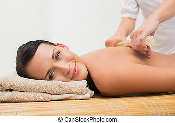 Beautiful brunette enjoying a bamboo roller massage smiling at c