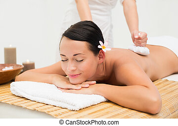 Peaceful brunette enjoying a herbal compress massage in the...