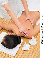 Woman enjoying a herbal compress massage in the health spa