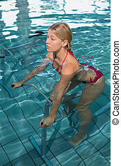 Fit blonde using underwater exercise bike in swimming pool...