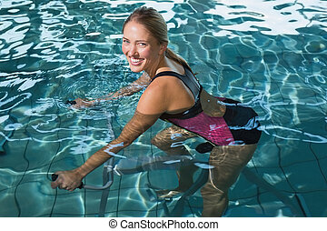 Fit happy blonde using underwater exercise bike in swimming...