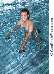 Fit brunette using underwater exercise bike in swimming pool...