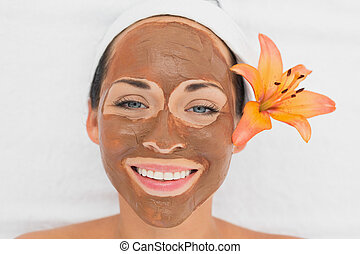 Smiling brunette getting a mud treatment facial in the...