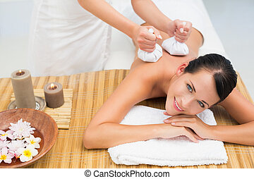 Peaceful brunette enjoying a herbal compress massage smiling...