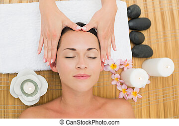 Smiling brunette enjoying a head massage in the health spa