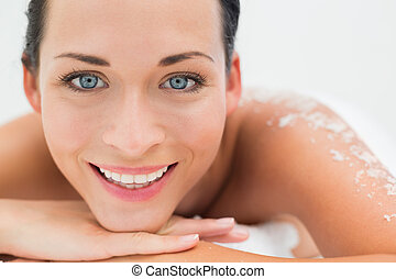 Peaceful brunette lying with salt scrub on back smiling at...