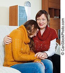Mature  mother gives solace to crying adult daughter at home