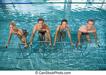 Fitness class doing aqua aerobics on exercise bikes in...