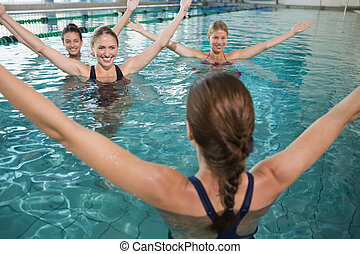Smiling female fitness class doing aqua aerobics in swimming...