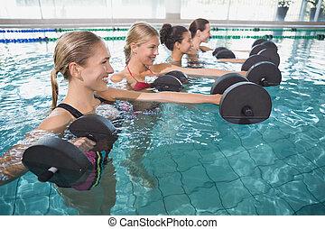 Smiling female fitness class doing aqua aerobics with foam...