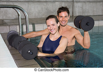 Happy couple working out with foam dumbbells in swimming...