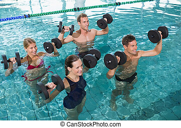 Happy fitness class doing aqua aerobics with foam dumbbells...