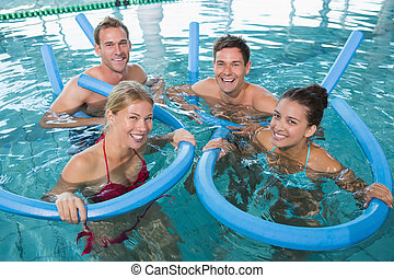Happy fitness class doing aqua aerobics with foam rollers in...