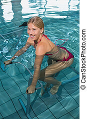 Fit blonde using underwater exercise bike smiling at camera...