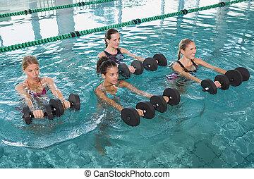 Female fitness class doing aqua aerobics with foam dumbbells...