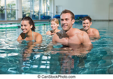 Fitness class using underwater exercise bikes in swimming...