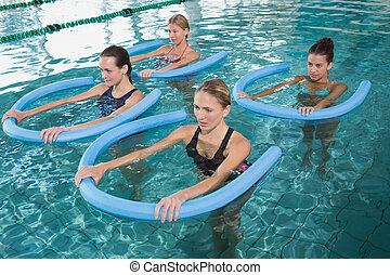 Fitness class doing aqua aerobics with foam rollers in...