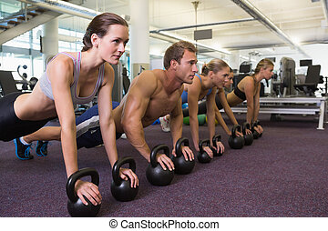 Fitness class in plank position with kettlebells at the gym