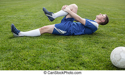 Football player in blue lying injured on the pitch on a...