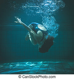 Athletic swimmer doing a somersault underwater in the...